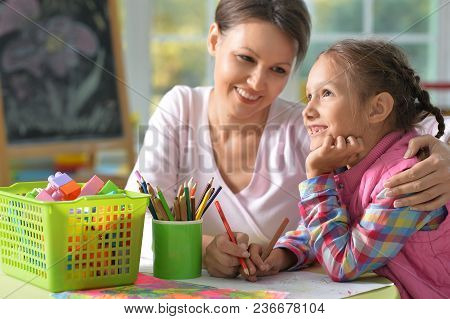Mother And Daughter Sitting At Table And Drawing With Pencils