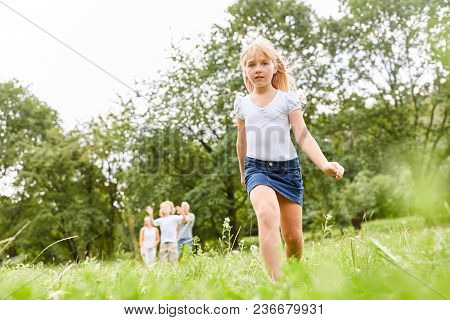 Blonde girl is going ahead on a trip in the family park