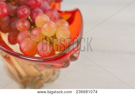 Bunch Of Fresh Ripe Pink Grapes In Glass Vase On Old Wooden Rustic White Planks