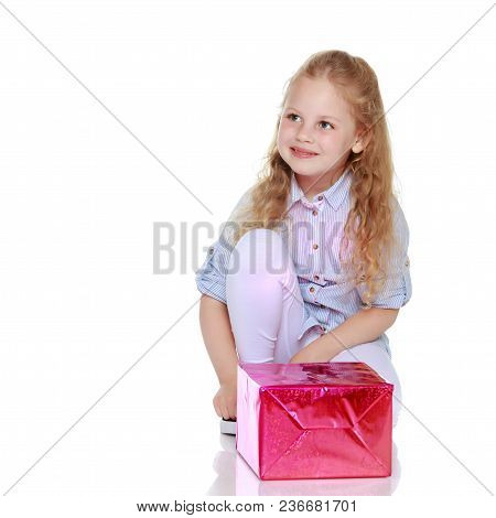 Beautiful Little Girl With A Gift On A White Background. Concept Of A Holiday, New Year And Christma