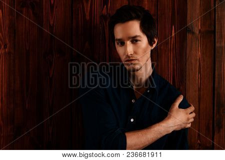 Vogue shot of a handsome male model in a denim shirt standing by a wooden wall. Men's beauty, fashion.
