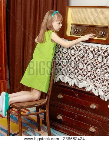 A Little Girl With Long Blond Hair And A Short Bangs, In A Short Summer Dress.the Girl Turns The Vol