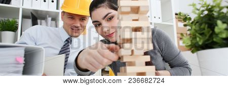 Businessman And Businesswoman Plays In Strategy Hand Rearranging Wooden Blocks Involved During Break