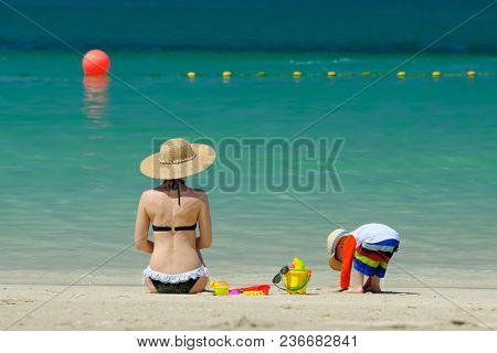 Two year old toddler boy playing with beach toys with mother on beach