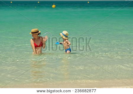 Two year old toddler boy on beach with mother