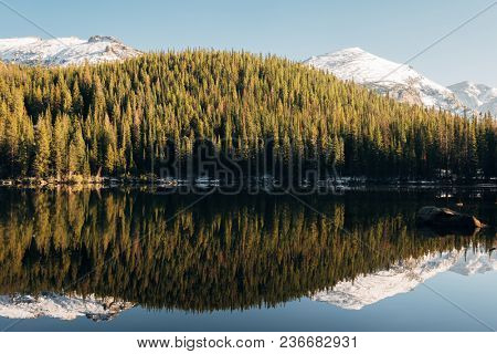Bear Lake and reflection with mountains in snow around at autumn. Rocky Mountain National Park in Colorado, USA.