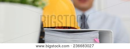 Businessman Engeneer Architect In Office On A Background Of Yellow Office And Folders With Papers