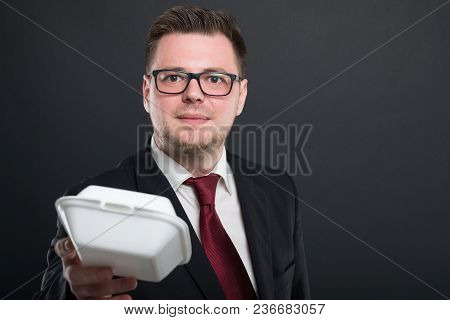 Portrait Of Business Man Handing Lunch Box.