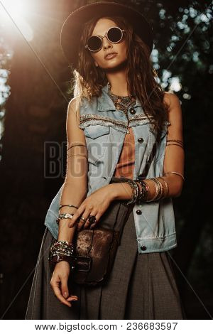 Denim style. Sexual young woman posing in jeans clothes on a street. Beauty, fashionable look. Boho style clothes and accessories.