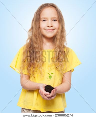 Child holding a sleedling. Girl with sprout