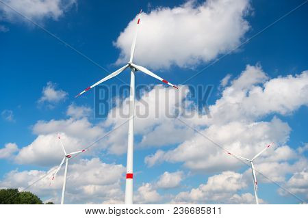 Wind Turbine On Cloudy Blue Sky. Alternative Energy And Electricity Source. Global Warming. Climate