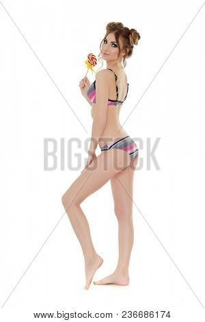 Cheerful young woman in bikini stands with lollipop on a white background. Pin up style.