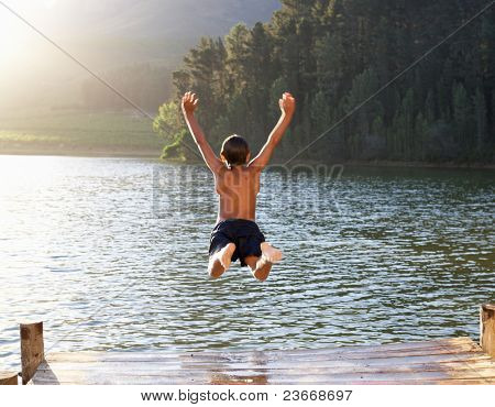 Young boy jumping into lake