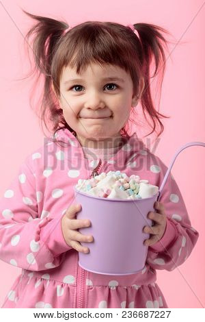 Portrait Of A Cute Little Girl Holding Small Violet Bucket Of Marshmallow, Isolated Over Pink Backgr