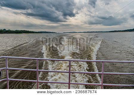 Trace On Water In Blue Sea In Manaus, Brazil. Sea Coast On Horizon On Cloudy Sky. Wanderlust Discove