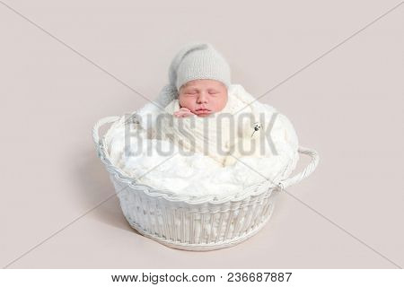 Newborn baby in white wrap laying on basket