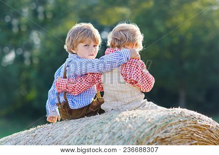Two Little Kid Boys, Twins And Siblings Sitting On Warm Summer Day On Hay Stack In Wheat Field. Happ