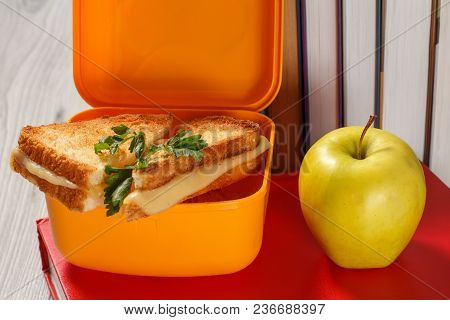 Yellow Sandwich Box With Toasted Slices Of Bread, Cheese And Green Parsley, Green Apple And Hardback