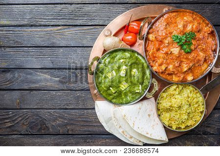 Different Bowls With Assorted Indian Food On Dark Wooden Background, Top View. Dishes And Appetizers