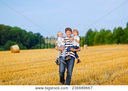 Happy Family Enjoying Sunset In Wheat Field. Beautiful Young Man With Two Adorable Toddler Kids Boys