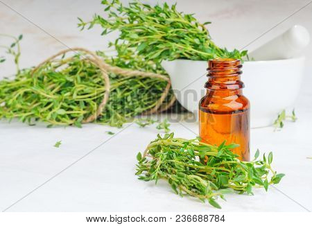 Thyme Essential Oil In Glass Bottle And Twigs On White Wooden Table.