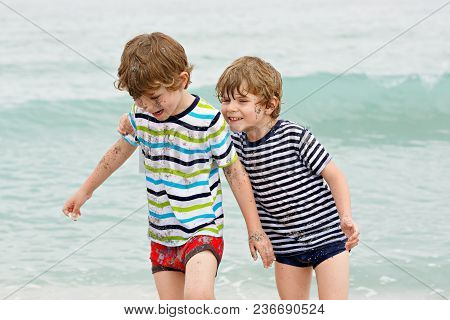Two Happy Little Kids Boys Running On The Beach Of Ocean. Funny Children, Siblings, Twins And Best F