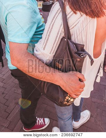 A Man Is Hugging A Woman While Standing On The Street.