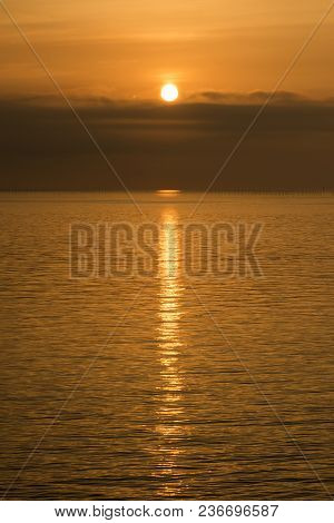 Orange View Of Gentle Sea Which A Sunbeam Reflected At Sunrise In Vertical Composition