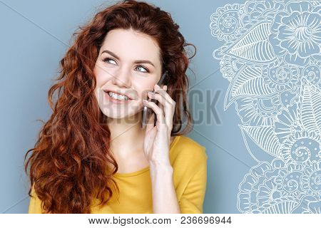 Pleasant Conversation. Pretty Smiling Student Looking Glad While Having A Pleasant Phone Talk With H