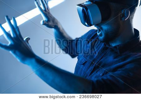 Bearded Man Wearing Vr Goggles And Touching Space In Blue Neon Light Amazed With Visual Effects.