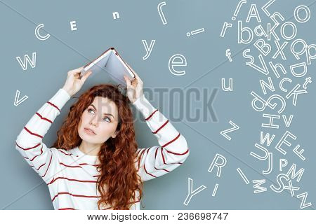 Learning Languages. Young Hardworking Student Putting A Notebook Above Her Head While Feeling Tired