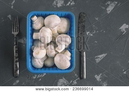 Fresh Mushrooms In A Blue Plastic Box With A Fork And A Knife. Dark Background, Close-up