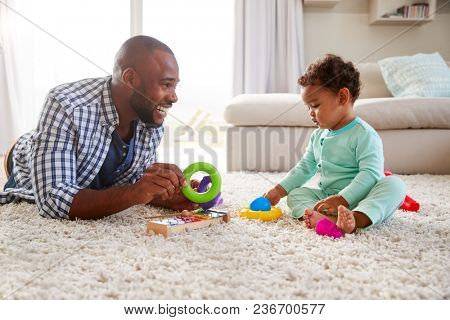 Black dad and toddler son playing on floor at home, close up