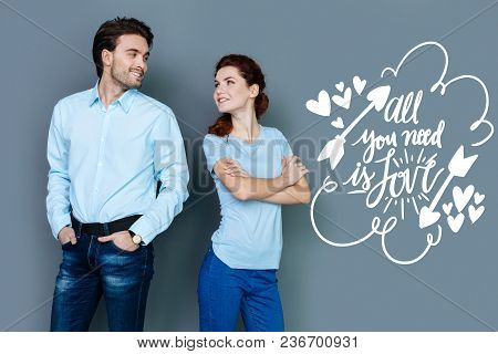 Happy Couple. Emotional Young Woman Standing With Her Arms Crossed And Smiling While Looking At Her