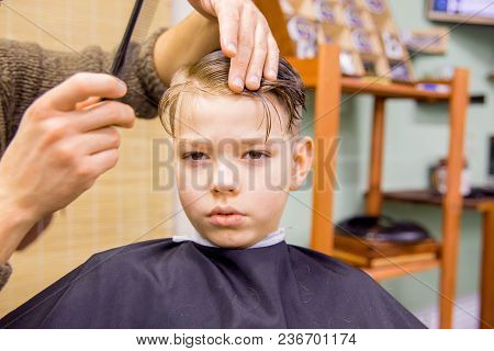 Boy Is Getting A Haircut In A Barbershop
