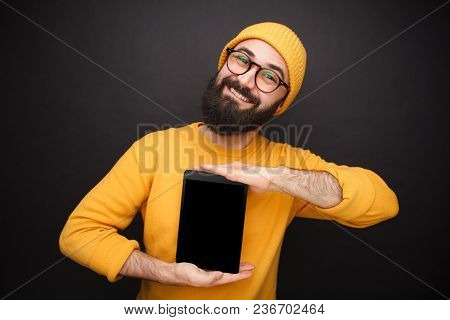 Handsome Bearded Man In Yellow Outfit Holding Black Touchpad Smiling At Camera.
