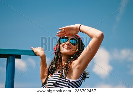 Girl In A Striped Dress And Sunglasses With A Smile Looks At The Sky Closing Her Hand
