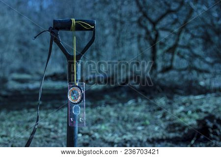 Compass Hanging On The Handle Of A Shovel On A Blurred Background Of A Mysterious Night Forest Aroun