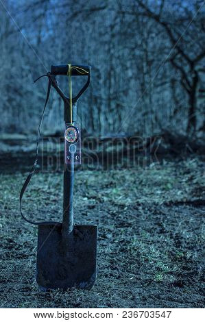 Compass Hangs On A Sapper Shovel On A Blurred Background Of Mysterious Trees At Night No One Around