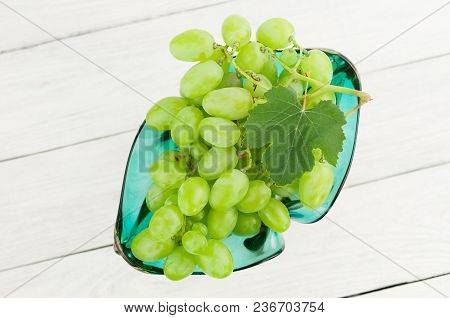 Bunch Of Fresh Ripe Green Grapes With One Leaf In Glass Vase On Old Wooden Rustic White Planks