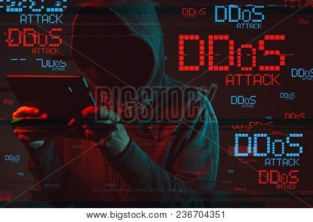 Distributed Denial Of Service Or Ddos Attack Concept With Faceless Hooded Male Person Using Tablet C
