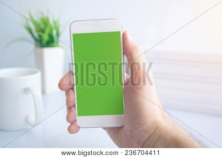 Using Smartphone During Coffee Break In The Morning, Male Hand Holding Mobile Phone With Blank Scree