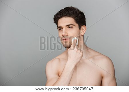 Beauty portrait of half naked confident young man using cotton pad on his face isolated over gray background