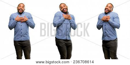 African american man with beard having charming smile holding hands on heart wanting to show love and sympathy