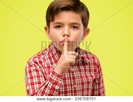 Handsome toddler child with green eyes with index finger on lips, ask to be quiet. Silence and secret concept over yellow background