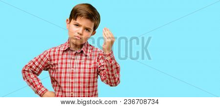 Handsome toddler child with green eyes angry gesturing typical italian gesture with hand, looking to camera over blue background