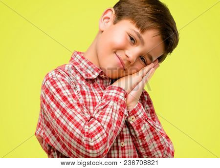 Handsome toddler child with green eyes tired and bored, tired because of a long day overworking over yellow background