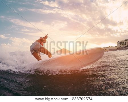 Fit Female Athlete Surfing At Sunset - Surfer Woman Performing Outdoor Inside Ocean- Extreme Sport,