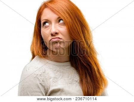 Beautiful young redhead woman making funny face fooling isolated over white background