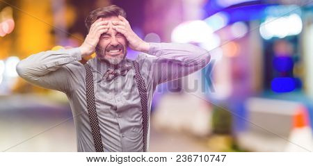 Middle age man, with beard and bow tie stressful keeping hands on head, terrified in panic, shouting at night club